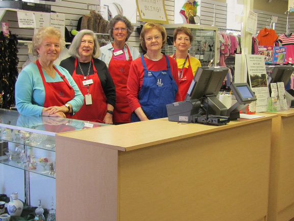 Smiling Assistance League ladies ready to ring up your purchase