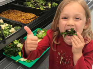 girls giving thumbs up to organic lettuce