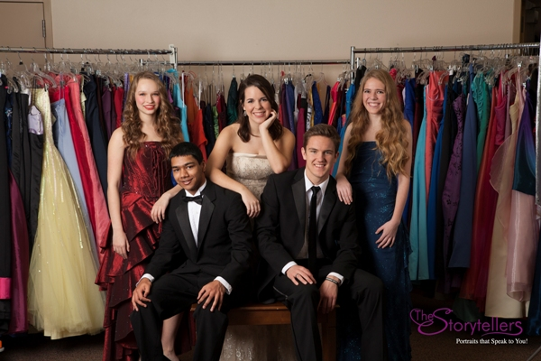 Teens posing wearing Cinderella's Closet gowns and tuxedos