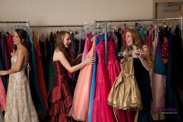 Three teens excitedly looking through Cinderella's Closet racks of gowns