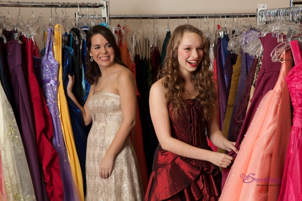 Two teens excitedly looking through Cinderella's Closet racks of gowns
