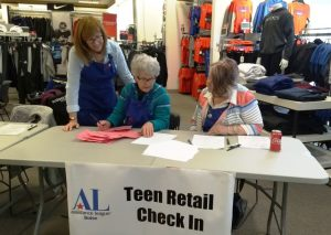 Members working at the Teen Retail check-in desk