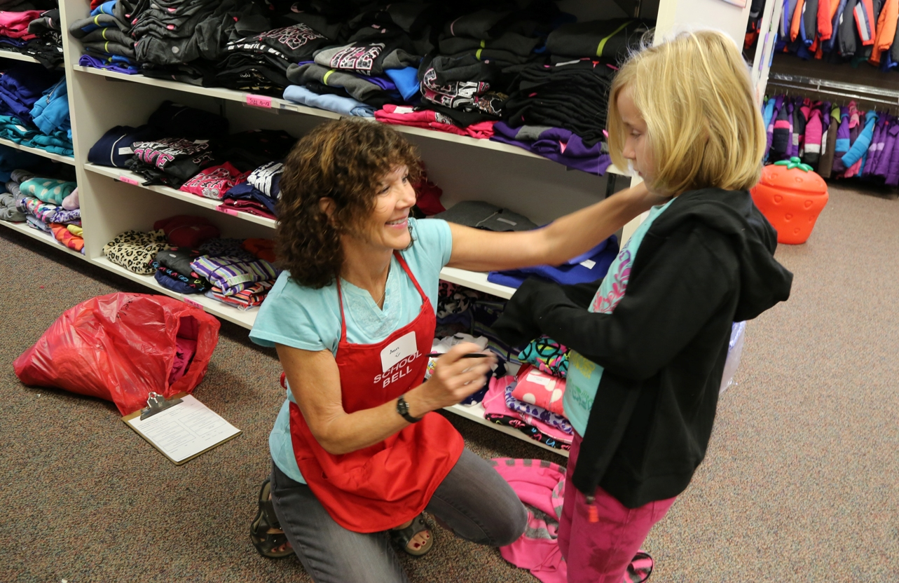 Member helping student try on sweatshirt at Operation School Bell
