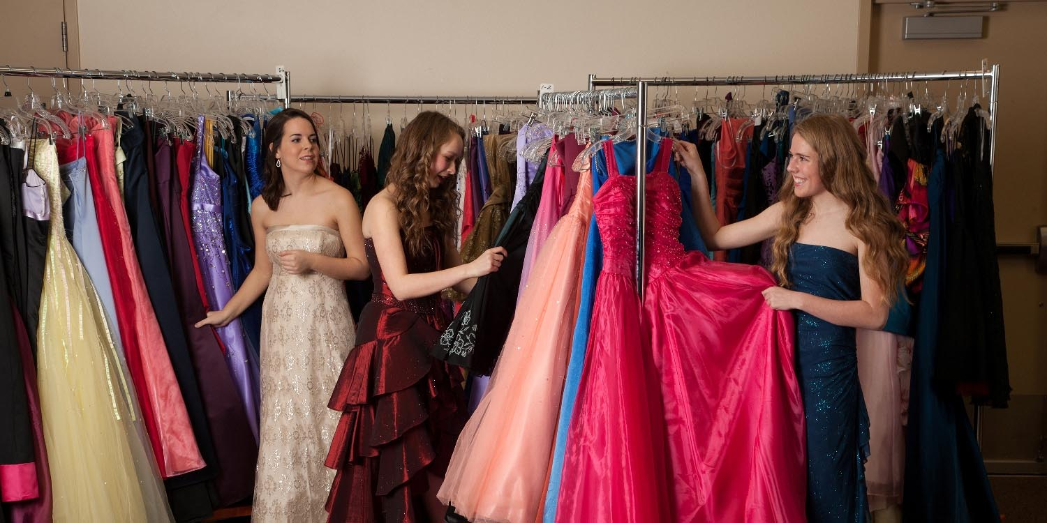 Teens admiring all the Cinderella Closet gowns on racks