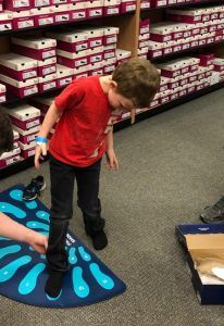 Boy shoe shopping at Canyon County Branch's first Operation School Bell event.
