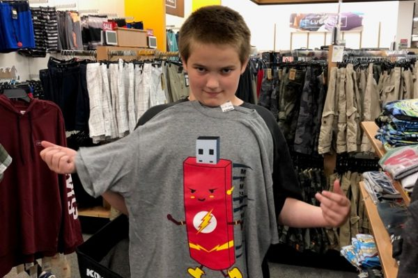Boy showing off his new shirt at Operation School Bell event.