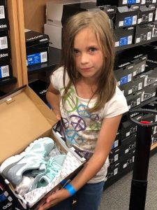 Girl shoe shopping at Canyon County Branch's first Operation School Bell event.