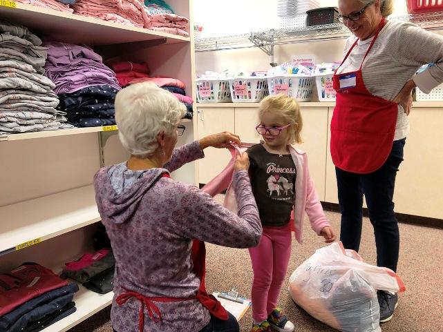 Girl trying on sweatshirt at Operation School Bell with help of member volunteers