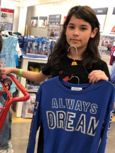"Teen showing a t-shirt she's selected that says ""Always Dream"""