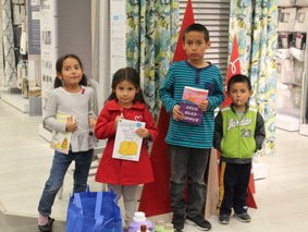 Cute kids at Operation School Bell shopping event showing off their books and clothing