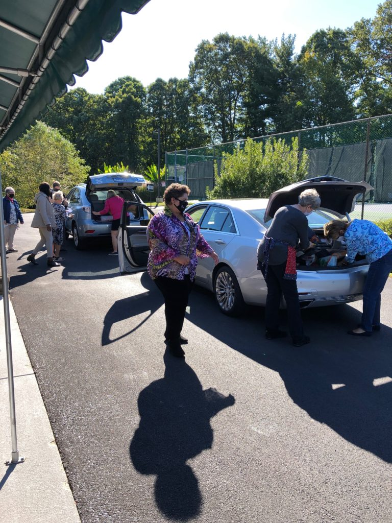 Members drive up to the Stork's Nest Baby Shower to donate items.