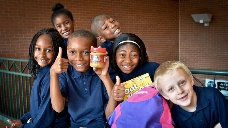 Six young students happily posing with food items donated by ALMSP