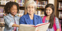 Senior adult teacher or librarian reads a book to elementary students in school classroom or library setting.  She is helping the girls learn to read or learn English.