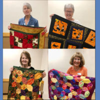 Winners of quilt fundraiser with quilts