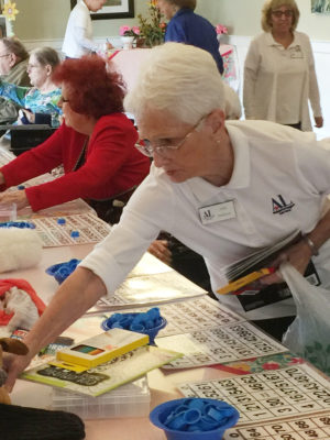 Volunteer Assisting Residents with Bingo cards