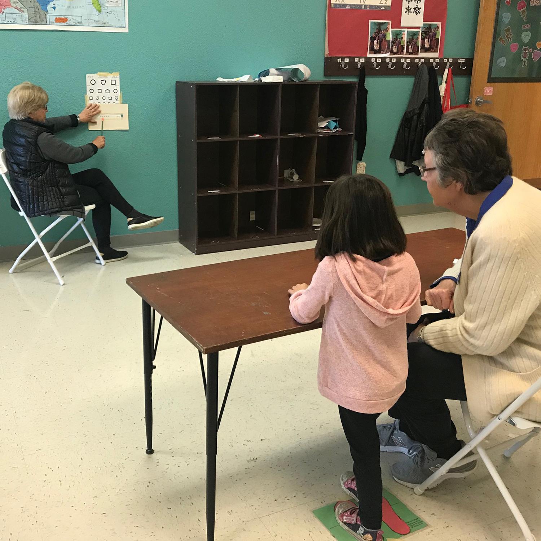 Volunteer and pre-schooler using the eye chart