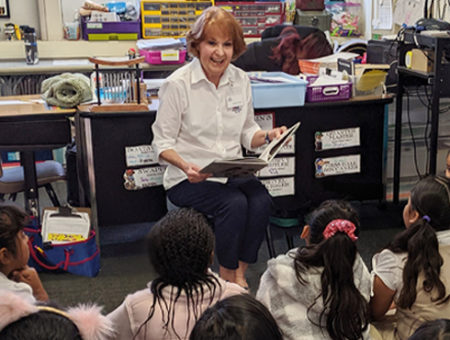 Readers Are Leaders volunteer reading to students