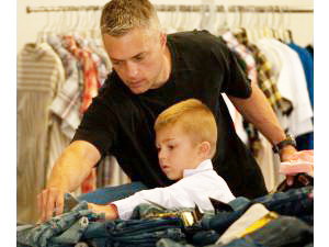 A Marine sergeant helps his son pick out a pair of jeans during Assistance League's back-to-school event at Camp Pendleton.