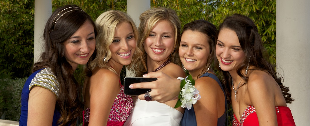 A group of five beautiful teenage girls dressed for the prom are taking a self portrait with a smart mobile phone.