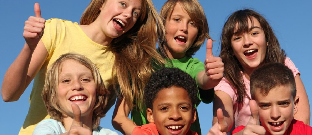 Diversity, mixed group of diverse kids tweens, or children holding thumbs up at summer camp