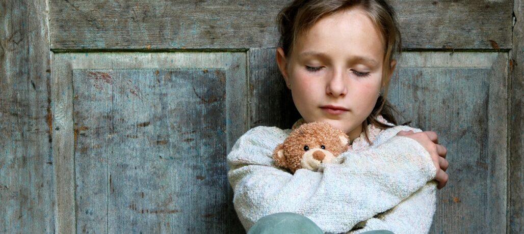Sad little girl with teddy bear