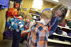 Wendy Brown, Fort Bliss Bugle Editor Maryanne Benson, right, and Flo McCloskey, back left, Operation School Bell volunteers, help a pair of Bliss Elementary School students find clothes at the organization's headquarters at 2728 E. Yandell Drive, El Paso, Jan. 26.