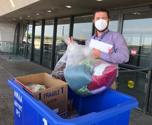 Man places bags in blue crate